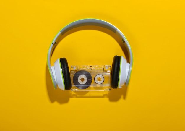 Stylowe bezprzewodowe słuchawki stereo i kaseta audio na żółtej powierzchni z cieniem