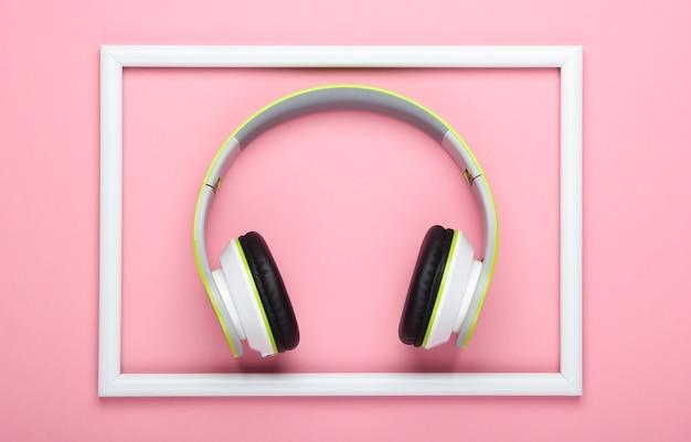 Stylowe bezprzewodowe słuchawki stereo na różowej, pastelowej powierzchni z białą ramką