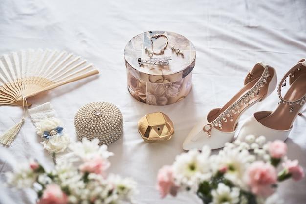 Stylowe białe ślubne buty ślubne, perfumy, kwiaty i biżuteria.