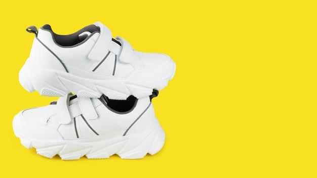 Stylowe białe trampki na kolorowym tle, do fitnessu lub sportu, kopia przestrzeń