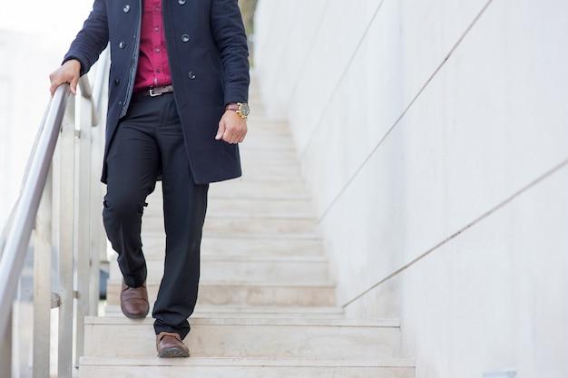 Stylowe biznesmen na sobie płaszcz schodząc na dół