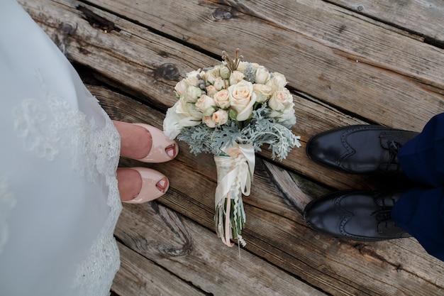 Stylowe buty panny młodej i pana młodego na drewnianej podłodze. delikatny bukiet ślubny na drewnianej desce z teksturą. buty damskie i męskie na drewnianej powierzchni. państwo młodzi. dzień ślubu cocept z bliska