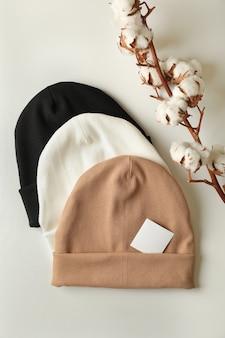 Stylowe czapki i bawełna na białej powierzchni