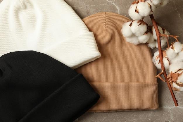 Stylowe czapki i bawełna na szarej powierzchni