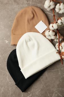 Stylowe czapki i bawełna na szarym tle