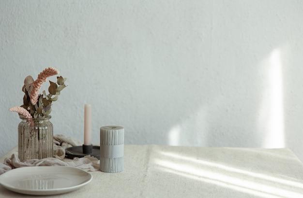 Stylowe detale wystroju wnętrza na tle białej ściany z promieniami słońca.