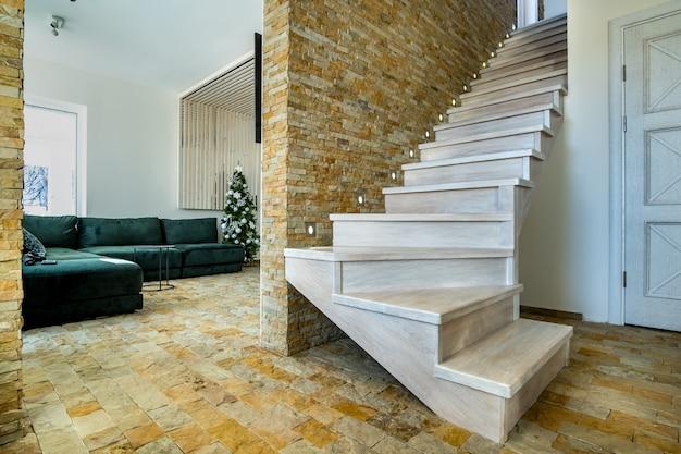 Stylowe drewniane współczesne schody wewnątrz wnętrza domu na poddaszu.