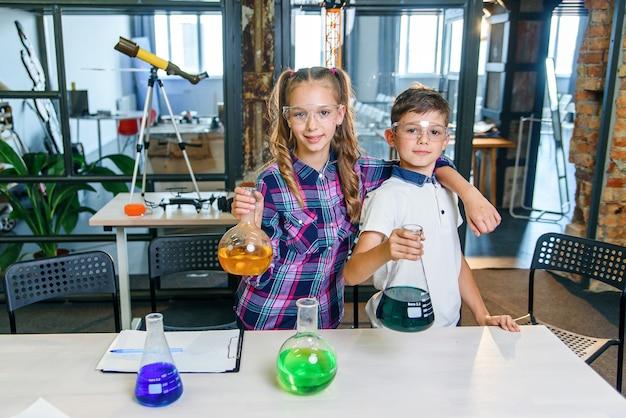 Stylowe dzieci w szkole w okularach ochronnych stoją tyłem do siebie w nowoczesnym laboratorium chemicznym i trzymają szklane kolby z kolorowymi płynami do eksperymentu naukowego w szkole podstawowej.