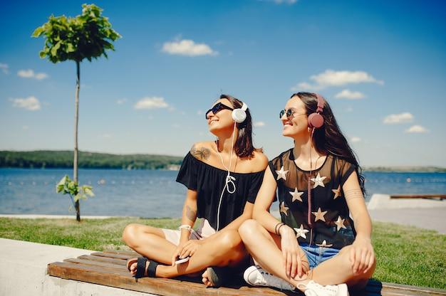 Stylowe dziewczyny chodzą w parku latem