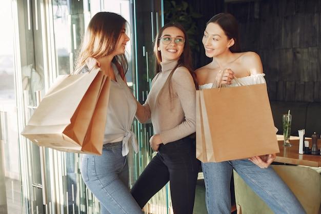 Stylowe dziewczyny stojące w kawiarni z torbami na zakupy