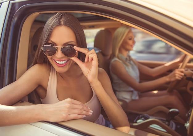 Stylowe dziewczyny uśmiechają się i bawią podczas jazdy samochodem.