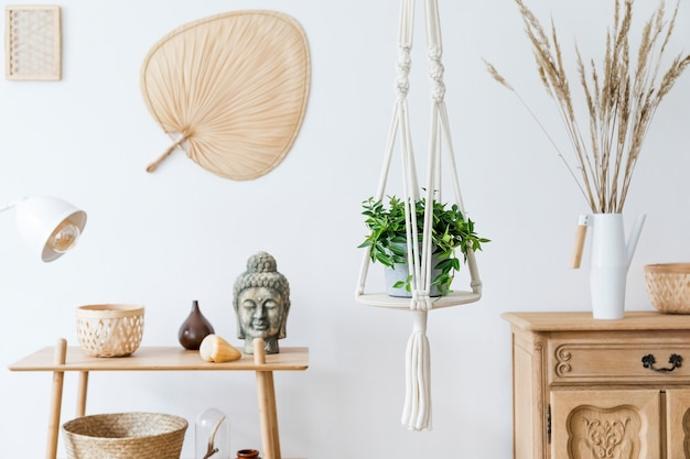 Stylowe i boho domowe wnętrze otwartej przestrzeni z drewnianym biurkiem, krzesłem, lampą i białą półką. design i eleganckie akcesoria osobiste. botanika i minimalizm. wystrój domu. malarstwo abstrakcyjne na ścianie