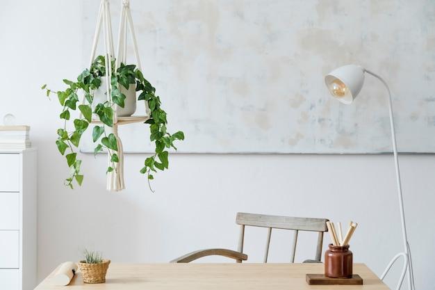 Stylowe i boho domowe wnętrze przestrzeni roboczej z drewnianą lampką na biurko i białą półką design i eleganckie dodatki osobiste botanika i minimalistyczny wystrój domu abstrakcyjne obrazy na ścianie