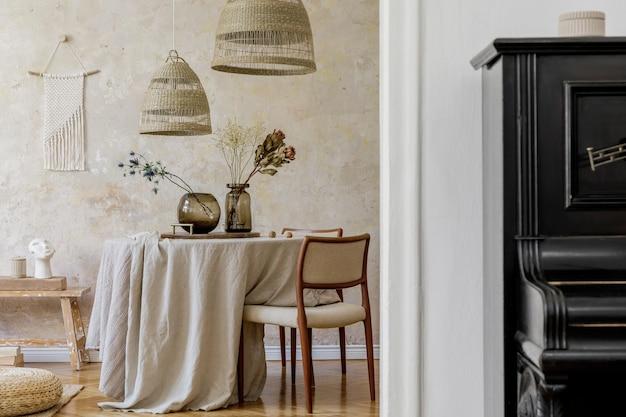 Stylowe i eleganckie wnętrze jadalni ze stołem jadalnym, designerskimi krzesłami, rattanowymi lampami wiszącymi, suszonymi kwiatami w wazonach, meblami, dekoracjami, pianinem i akcesoriami osobistymi w przytulnym wystroju domu.