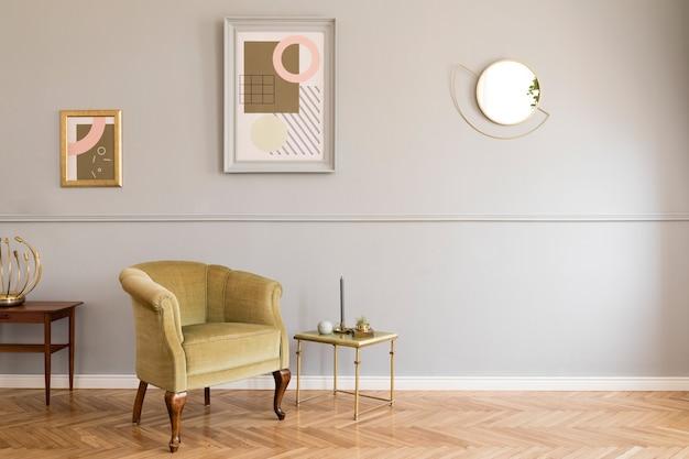 Stylowe i luksusowe wnętrze salonu z eleganckim zielonym fotelem, stolikami w stylu retro, designerskimi lampami, eleganckimi dodatkami, złotym lustrem i ramkami makiety na szarej ścianie. szablon.