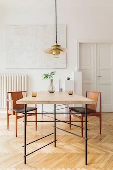 Stylowe i nowoczesne wnętrze jadalni z designerskim stołem, krzesłami, złotą lampą wiszącą, abstrakcyjnymi obrazami i eleganckimi dodatkami. tropikalne liście w wazonie. eklektyczny wystrój domu.