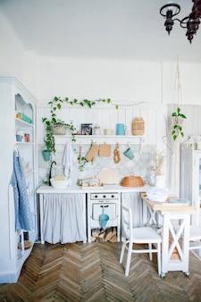 Stylowe i słoneczne wnętrze kuchni z małym drewnianym stołem w studio fotograficznym. skandynawski wystrój pokoju z akcesoriami kuchennymi.