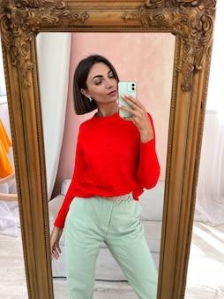 Stylowe kobiety w domu w jaskrawoczerwonym swetrze i miętowozielonych spodniach robią sobie zdjęcie w lustrze na telefonie