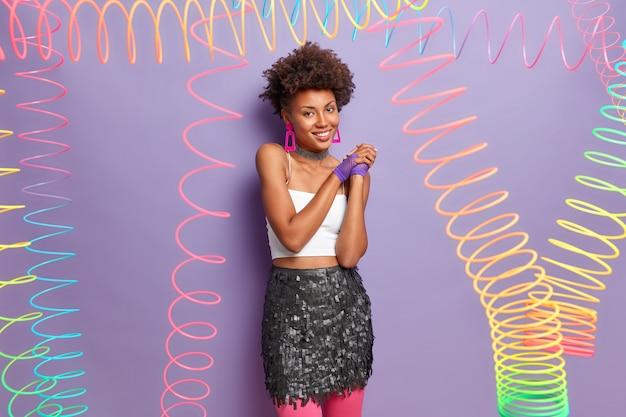 Stylowe, ładna kobieta ubiera się na specjalne okazje, przygotowuje się na imprezę młodzieżową, ma kręconą fryzurę, nosi top i spódnicę, uśmiecha się przyjemnie