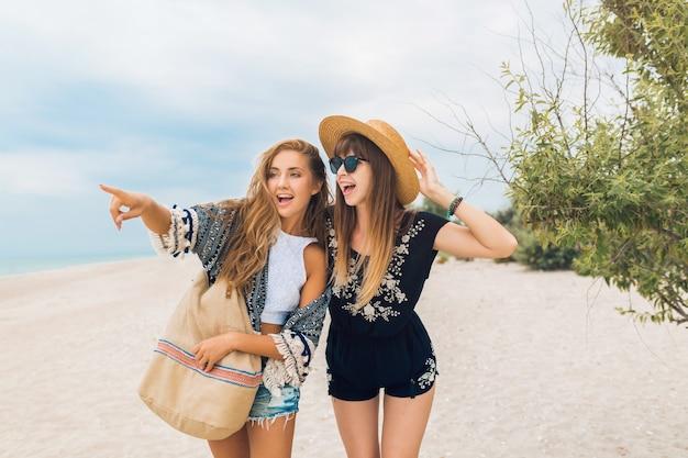 Stylowe ładne kobiety na letnich wakacjach na tropikalnej plaży, styl bohemy, przyjaciele razem, akcesoria modowe, uśmiechnięta, radosna emocja, pozytywny nastrój, wskazujący palec, podróżujący turyści
