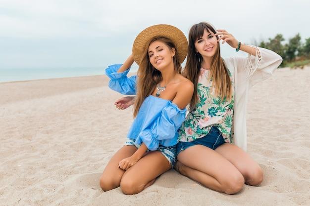 Stylowe ładne kobiety siedzą na piasku na wakacjach na tropikalnej plaży, słomkowy kapelusz