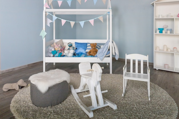 Stylowe meble w przestronnym monochromatycznym pokoju dziecięcym. nowoczesne wnętrze sypialni z małym, zdobionym łóżkiem dla dziecka. tradycyjny koń na biegunach