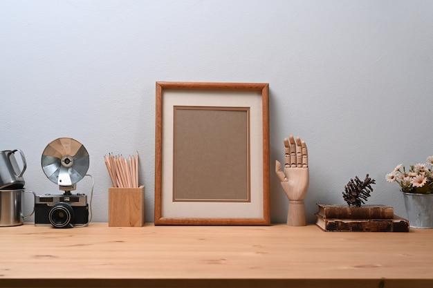 Stylowe miejsce pracy z brązową ramką na zdjęcia, aparatem i książkami na drewnianym stole.