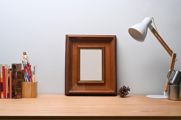 Stylowe miejsce pracy z pustą ramką na zdjęcia, lampą, uchwytem na ołówek i książką na drewnianym stole.