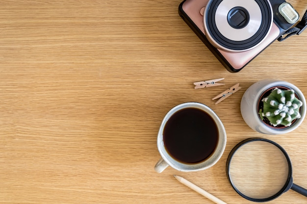 Stylowe mieszkanie leżał biznes skład na drewnianym biurku z aparatem fotograficznym, kaktusy, długopis, miejsce i materiały biurowe w nowoczesnej koncepcji.