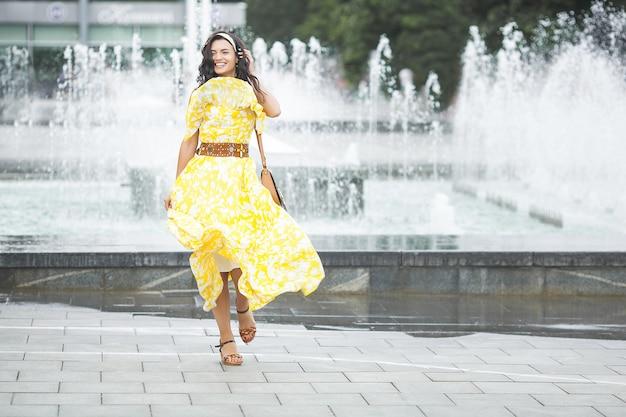 Stylowe młoda kobieta spaceru. miejska dziewczyna. modna kobieta. pełny wzrost strzelał piękna kobieta w żółtej sukni.