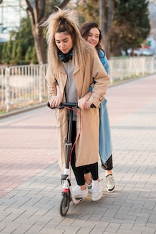 Stylowe młode kobiety jadące skuterem elektrycznym