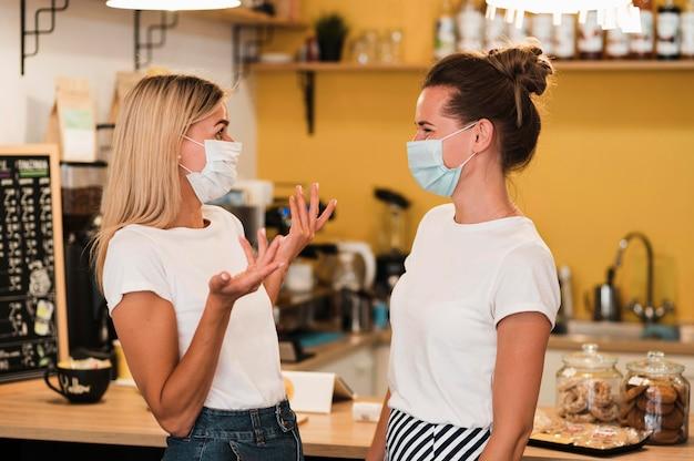 Stylowe młode kobiety noszące maski na twarz