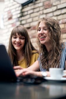 Stylowe młode kobiety odbywają przyjacielskie spotkanie przy filiżance kawy podczas korzystania z laptopa