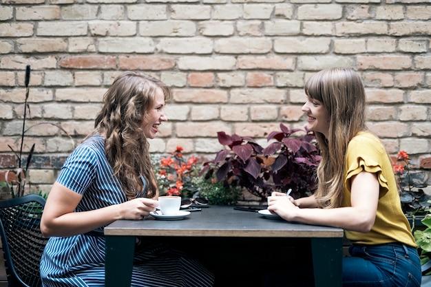 Stylowe młode kobiety odbywają przyjacielskie spotkanie przy filiżance kawy, siedząc przy stole i rozmawiając