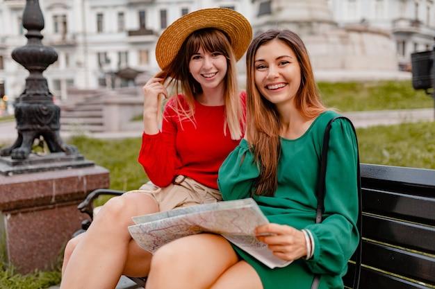 Stylowe młode kobiety podróżujące razem po europie ubrane w modne wiosenne stroje i dodatki