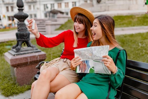 Stylowe młode kobiety podróżujące razem po europie ubrane w modne wiosenne sukienki i dodatki