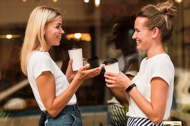 Stylowe młode kobiety razem cieszyć się kawą