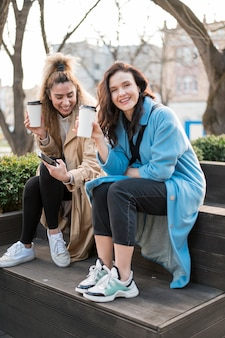Stylowe młode kobiety razem piją kawę