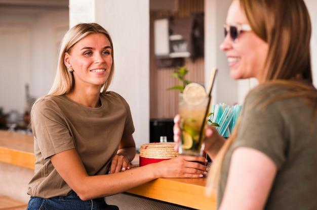 Stylowe młode kobiety razem piją koktajle