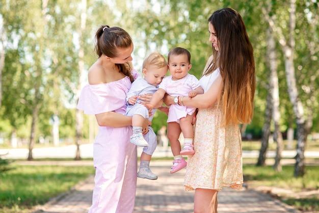 Stylowe młode matki spacerujące w parku miejskim z córkami. piękne dziewczynki bawią się ze sobą.