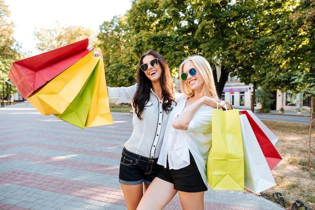 Stylowe młode panie w okularach przeciwsłonecznych idące ulicą z torbami na zakupy
