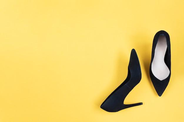 Stylowe moda czarne buty na obcasie na żółtym tle. płaskie świeckich, modne tło widok z góry. wygląd bloga modowego. dodaj swój tekst.