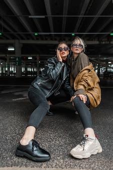 Stylowe modelki dziewczyny w modnych ubraniach z klasycznymi skórzanymi kurtkami w czarnych dżinsach z butami pozują na parkingu w mieście