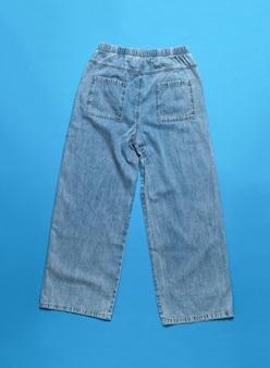 Stylowe modne szerokie dżinsy damskie ocieplane na białej powierzchni