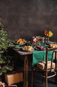Stylowe nakrycie stołu na świąteczny rodzinny obiad z choinką w tle i prezentami na...