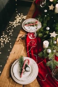 Stylowe nakrycie stołu z płonącymi świecami i świątecznymi dekoracjami