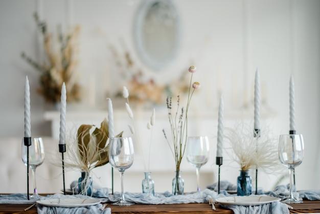Stylowe nakrycie stołu z suszonymi kwiatami. talerz z rocznika złotym widelcem i nożem, świecami, zakurzone niebieskie serwetki na drewnianym stole. zimowa dekoracja ślubna.