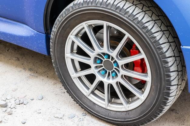 Stylowe niebieskie koło samochodowe z czerwonym zaciskiem hamulca