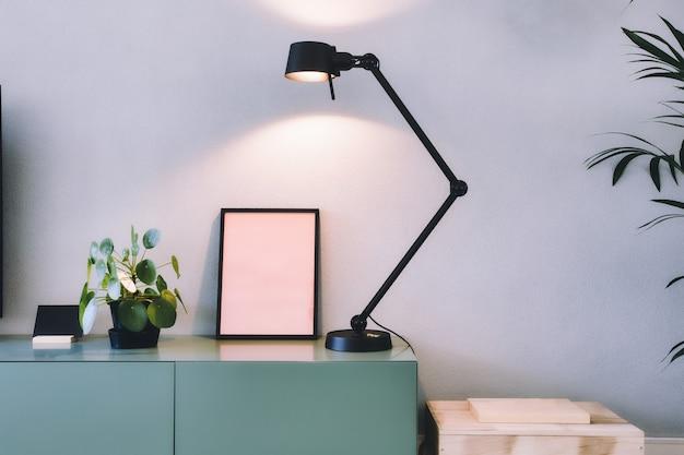 Stylowe nowoczesne wnętrze, pusta ramka na zdjęcia z czarną lampą i zieloną rośliną chińskich pieniędzy, retro naleśnikarnia na zielonym stole w stylu skandynawskim