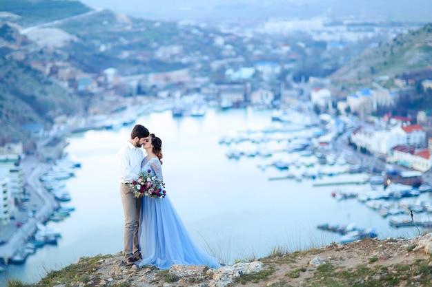 Stylowe nowożeńcy wtulają się w naturę, na tle skał i klifów